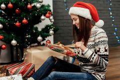 Happy woman opening christmas present box. girl in sweater with Royalty Free Stock Photography