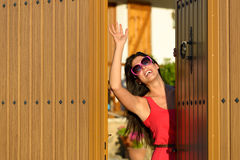 Happy woman opening door and welcoming. Happy woman opening her country house door to welcome guests visitors. Charming caucasian brunette girl good bye standing Stock Photography