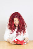 Happy woman opening a gift box. Portrait of a happy redhead woman opening a red gift box. Happy emotion Stock Images