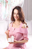 Happy woman opening gift box with present. Smiling beautiful brunette ready to see surprise. Joy, happiness, birthday, holiday , new year concept Stock Image