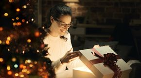 Woman opening a magical Christmas gift royalty free stock image