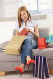 Happy woman opening shopping bags. Sitting on sofa, smiling Stock Photo