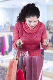 Happy woman opens shopping bags at mall Royalty Free Stock Image