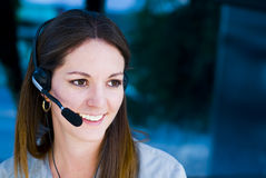 Happy woman operator. Happy operator woman in talking with headset telephone in blue background Royalty Free Stock Image