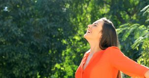 Woman in orange breathing fresh air in a park stock footage