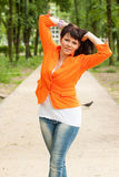 Happy woman in orange jacket Stock Photos