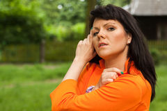 Happy woman in orange jacket Stock Image