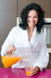 Happy woman with orange juice at domestic kitchen Royalty Free Stock Images