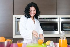 Happy woman with orange juice at domestic kitchen Royalty Free Stock Photo