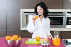 Happy woman with orange juice at domestic kitchen Stock Image