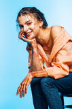 Happy woman in orange shirt sitting on blue background Stock Image