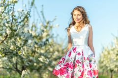 Happy Woman in an orchard at springtime. Enjoying sunny warm day. Retro style dress. Blooming blossom cherry trees royalty free stock photo