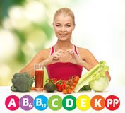 Happy woman with organic food and vitamins. People, healthy eating, vegetarian and health care concept - happy woman with organic food and vitamins over green Stock Photos