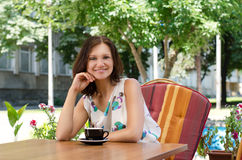 Happy woman at outdoor restaurant. Happy woman seated in a comfortable chair at a table at an outdoor restaurant enjoying a cup of coffee Stock Images