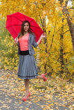 Happy woman outdoor with an umbrella. Happy woman outdoor in autamn with red umbrella stock photo