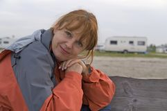 Happy woman outdoors. Portrait of happy ginger haired woman outdoors with sand and caravan in background stock photography