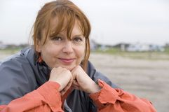 Happy woman outdoors. Portrait of happy middle aged woman with ginger hair on beach stock photography