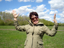 Happy woman outdoors. Happy middle aged woman with sunglasses on field with cloudscape in background Stock Image