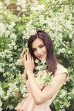 Happy woman outdoors in blossom summer flowers garden Royalty Free Stock Photos