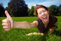 Happy woman outdoors holding thumbs Stock Photos