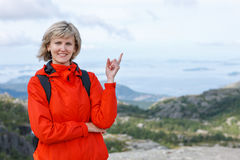 Happy woman outdoors pointing up Royalty Free Stock Image
