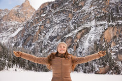 Happy woman outdoors among snow-capped mountains rejoicing Stock Images