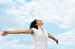 Happy woman with outspread arms. Happy smiling woman standing with outspread arms and her face lifted to the cloudy blue sky Royalty Free Stock Photo