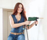 Happy woman in overalls with drill Stock Photos