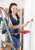Happy woman in overalls paints wall Royalty Free Stock Photo