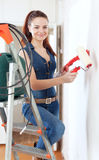 Happy woman in overalls paints wall Royalty Free Stock Photos
