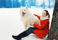 Happy woman owner having fun with white Samoyed dog outdoors Stock Photography