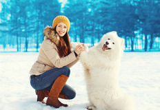 Happy woman owner playing with white Samoyed dog in winter Royalty Free Stock Photo
