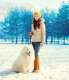 Happy woman owner walking with white Samoyed dog in winter Royalty Free Stock Photography