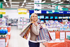 Happy woman with packages for purchases in store Royalty Free Stock Image