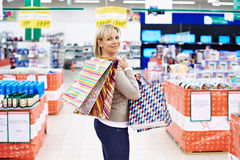 Happy woman with packages for purchases in store Royalty Free Stock Photography