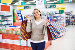 Happy woman with packages for purchases in store Royalty Free Stock Photo