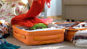 Happy woman packing a luggage for a new journey. Slow motion. Dolly stock video