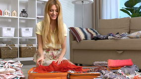 Happy woman packing a luggage for a new journey. Slow motion. Dolly stock video footage