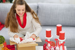 Happy woman packing parcel with Christmas gift Royalty Free Stock Photos