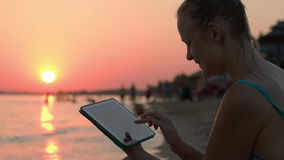 Happy woman with pad on beach at sunset. Happy young woman using tablet computer on beach at sunset. Evening sun, sea and people on background stock footage