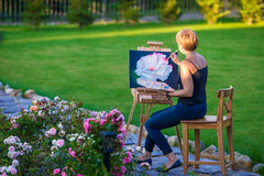 Happy woman painting a picture on an easel on a Royalty Free Stock Images