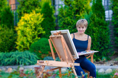 Happy woman painting a picture on an easel on a Royalty Free Stock Photos