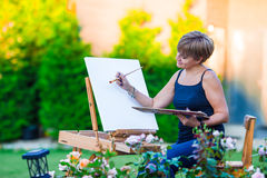 Happy woman painting a picture on an easel on a Stock Image
