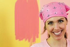 Happy Woman painting pink wall. A woman wearing a pink bandanna with a big smile.  She is painting pink paint on a yellow wall Stock Images