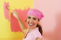 Happy Woman Painting Pink and Yellow. A happy woman painting a yellow wall with pink paint Stock Image