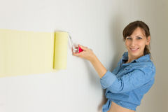 Happy woman painting the wall. Happy smiling woman painting the wall with roller Royalty Free Stock Images