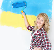 Happy woman painting wall at room Stock Images