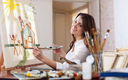 Happy  woman paints home of dreams on canvas Royalty Free Stock Photo
