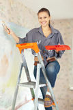 Happy woman paints wall Royalty Free Stock Images