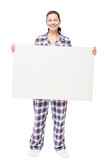 Happy woman in pajamas holds a huge poster in front of a white Royalty Free Stock Photography